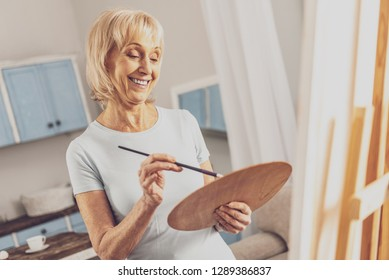 Create idea. Pleased mature woman keeping smile on her face while painting picture