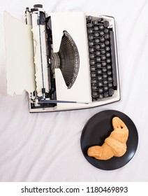Create inspiring atmosphere before start writing new page with typewriter. Typewriter and delicious croissant plate lay white bed sheets. Benefit being writer is comfortable inspiring workplace.