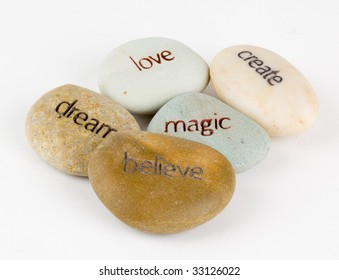 Create, magic, believe, dream, and love wording engraved on stones.