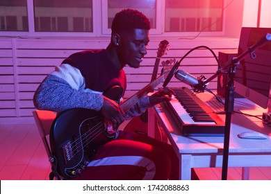 Create music and a recording studio concept - african american man guitarist recording electric guitar track in home studio