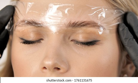 Create permanent eyebrow makeup. Microblading eyebrows work flow in a beauty salon. Cosmetician putting on film on eyebrows. Permanent makeup for eyebrows. Eyebrow lamination and styling