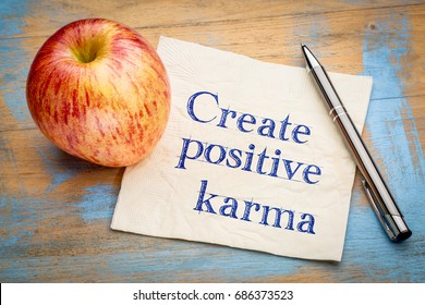create positive karma - inspirational handwriting on a napkin with apple, positivity concept