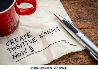 create positive karma now - motivational handwriting on a napkin with cup of coffee