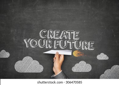 Create your future concept on black blackboard with businessman hand holding paper plane