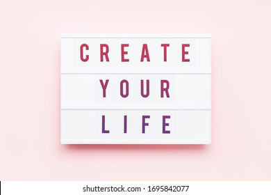 CREATE YOUR LIFE written in light box on pink background. Motivation quote. Top view.