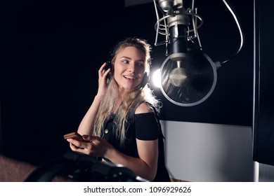 Create your music! Beautiful young girl smiling, while reading lyrics and singing a song with a mobile phone in the recording studio.