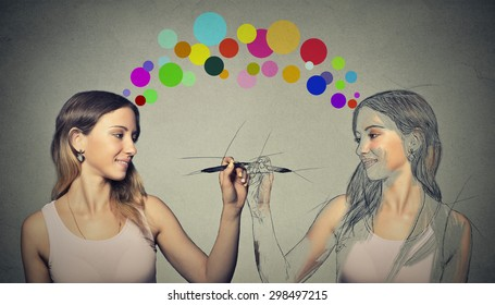 Create yourself, your future destiny, image concept. Attractive young woman drawing a picture, sketch of herself on grey wall background. Human face expressions, determination, creativity perception