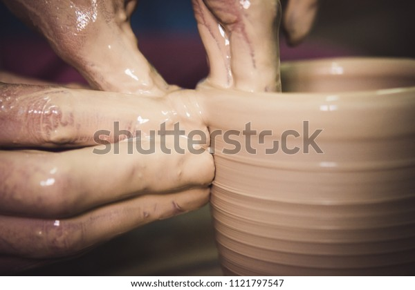 Creating ceramic products of white clay close-up. The sculptor in workshop makes clay jug closeup. Master crock. Twisted potter's wheel. Art creativity Cultural tradition Handmade Craft Master's Hands