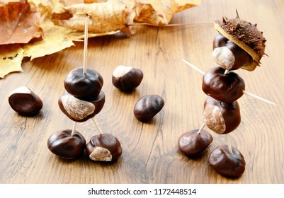Creating Chestnut figures made of nuts. Maple leaves in background. tinkering with autumn season items.