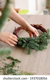 Creating a Christmas wreath of spruce branches, balls and stars. Decoration for the house for Christmas. Concept of florist's work before christmas holidays.