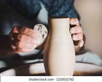 Creating earthenware and traditional pottery concept. Experienced male potter's hands creating beautiful clay product - vase - using professional tools