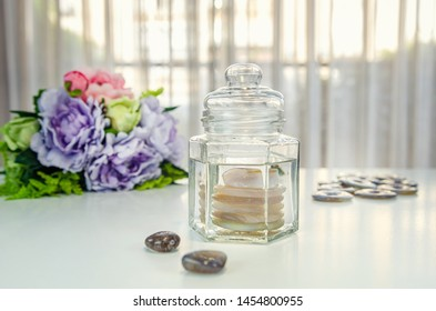 Creating a gem elixir by using smokey quartz stones for transmuting negative energy. There are glass jar with water, donuts stones on the table. A bouquet of flowers out of focus in the background