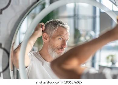 Eine Frisur schaffen. Morgens kämmt sich ein Mann das Haar