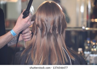 Creating hairstyles masters in the salon on the woman's head curls.