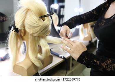Creating hairstyles on a mannequin. Training hair styling on a mannequin.