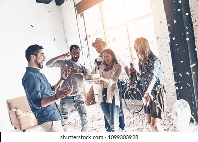 Creating happy memories. Happy young man celebrating birthday among friends while standing in room with confetti flying around