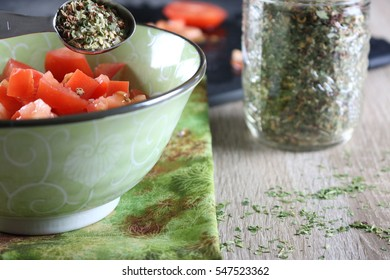Creating healthy homemade goodness, spices being mixed in with organic tomatoes in a green bowl