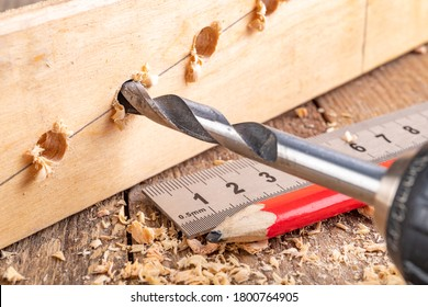 Creating holes with a metal drill in a piece of wood. Metal ruler for measuring the distance between the holes. Light background.