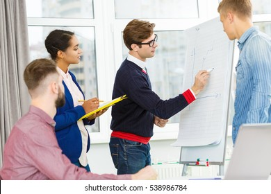 Creating ideas. Young handsome project manager leading the meeting of a creative team in the office drawing on the flipchart brainstorming with his colleagues teamwork concept
