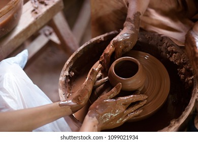 Creating jar or vase of clay close-up. Master crock. Man hands making clay jug macro. sculptor in workshop jug out of earthenware closeup. Twisted potter's wheel