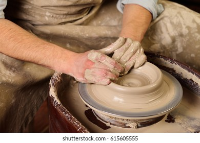 Creating a jar or vase. Master crock. Man hands making clay jug. The sculptor in the workshop makes a jug out of earthenware closeup. Potter's wheel. Pottery concept.