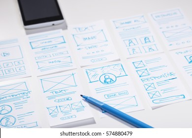 Creating mobile responsive website, wireframe sketches and blue marker pen on designer desk