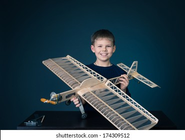 Creating the model plane. Happy boy holding wooden model plane.