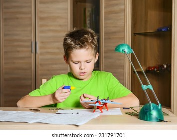 Creating the model plane. Happy boy making aircraft model. Hobby concept.