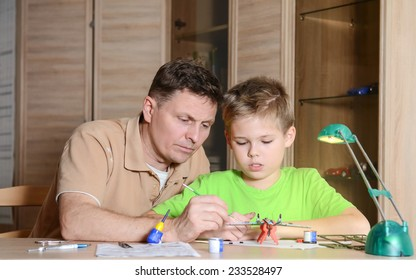 Creating the model plane. Happy son and his father are making aircraft model. Hobby and family  concept.