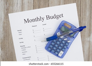 Creating a monthly budget, A print out of a monthly budget with pen and calculator on weather wood