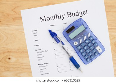 Creating a monthly budget, A print out of a monthly budget with pen and calculator on a desk