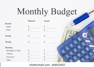 Creating a monthly budget, A print out of a monthly budget with pen and calculator