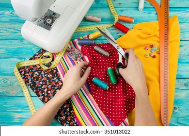 Creating a new fashion. Sewing Process - Women's hands behind her sewing.  Sewing machine with many sewing utensils on ablue wooden table. Top view.