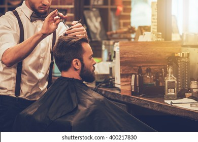 Creating new hair look. Young bearded man getting haircut by hairdresser while sitting in chair at barbershop