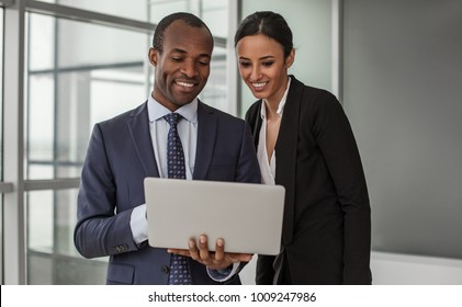 Creating new ideas. Portrait of positive young business partners wearing formal clothes are standing in office. Man is holding laptop and they are looking at screen of gadget with wide smile