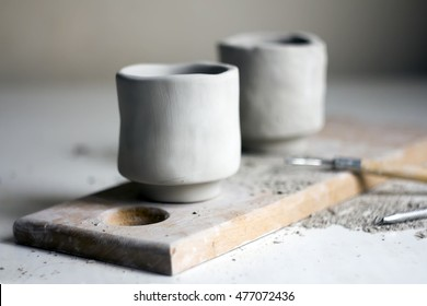 Creating a pair of handmade ceramic tea bowls. Working process without using a potter's wheel. White clay and pottery tools.