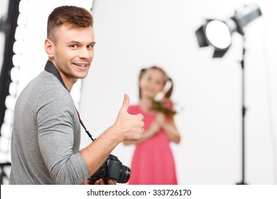 Creation time. Nice-looking male photographer shows thumbs up and smiles before making photos of his little model.