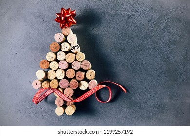 Creative 2019 wine cork Christmas tree decorated with a red foil ribbon and bow over a mottled blue background with copy space for a seasonal greeting