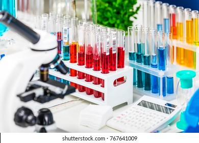 Creative abstract chemistry development, medicine, pharmacy, biology, biochemistry and research technology concept: table with scientific chemical laboratory equipment - microscope and test tubes