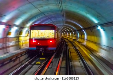 Creative abstract urban city transporation transit technology industrial business concept: red metro train in subway underground tunnel station platform with motion blur effect
