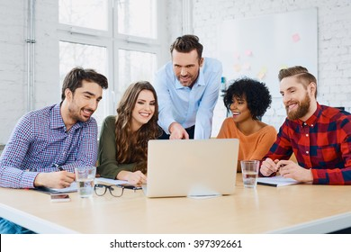 Creative agency coworkers discussing new project on laptop