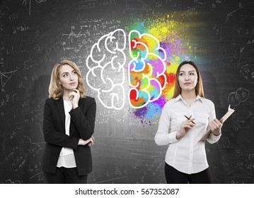 Creative and analytical thinking concept. Asian and european females on chalkboard background with creative brain drawing
