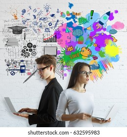 Creative and analytical thinking concept. Young man and woman using laptops on brick background with colorful sketch and mathematical formulas