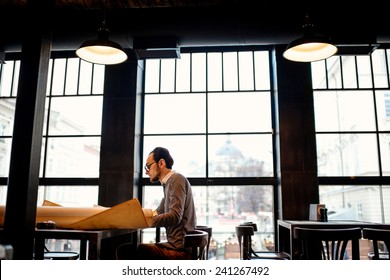 Creative architect projecting with pencil on the big drawings in the dark loft office or cafe. General plan with windows