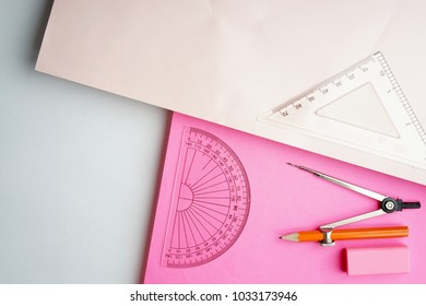 Creative arrangement of geometry stationery like protractor, set squares, eraser, metal compass on pastel papers. Interpretation of education in mathematics, architecture and engineering.Flat lay view