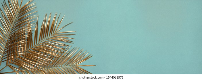 Creative arrangement of natural golden painted date palm branches on muted cyan blue background. Artistic floral luxury floral border frame design. Wide format tropical poster, banner template.