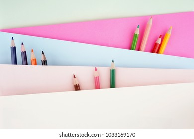 Creative arrangement of stationery such as color pencils on pastel colored papers looking like the pencils are on an escalator. Conceptual interpretation of education theme. Flat lay view.
