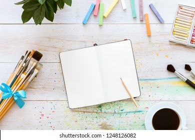 Creative art designer workplace, artistic mock up, blank notebook for sketches with pencil on it, set of paintbrushes and cup of coffee on white wooden table, top view, copy space, flat lay style