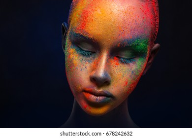 Creative art make up. Holi colors. Closeup cropped studio portrait of young fashion model with bright colorful mix of paint on her face.