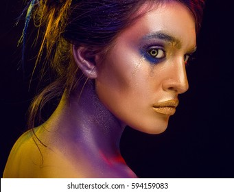 Creative art makeup. Close-up studio portrait of young fashion model on a black background